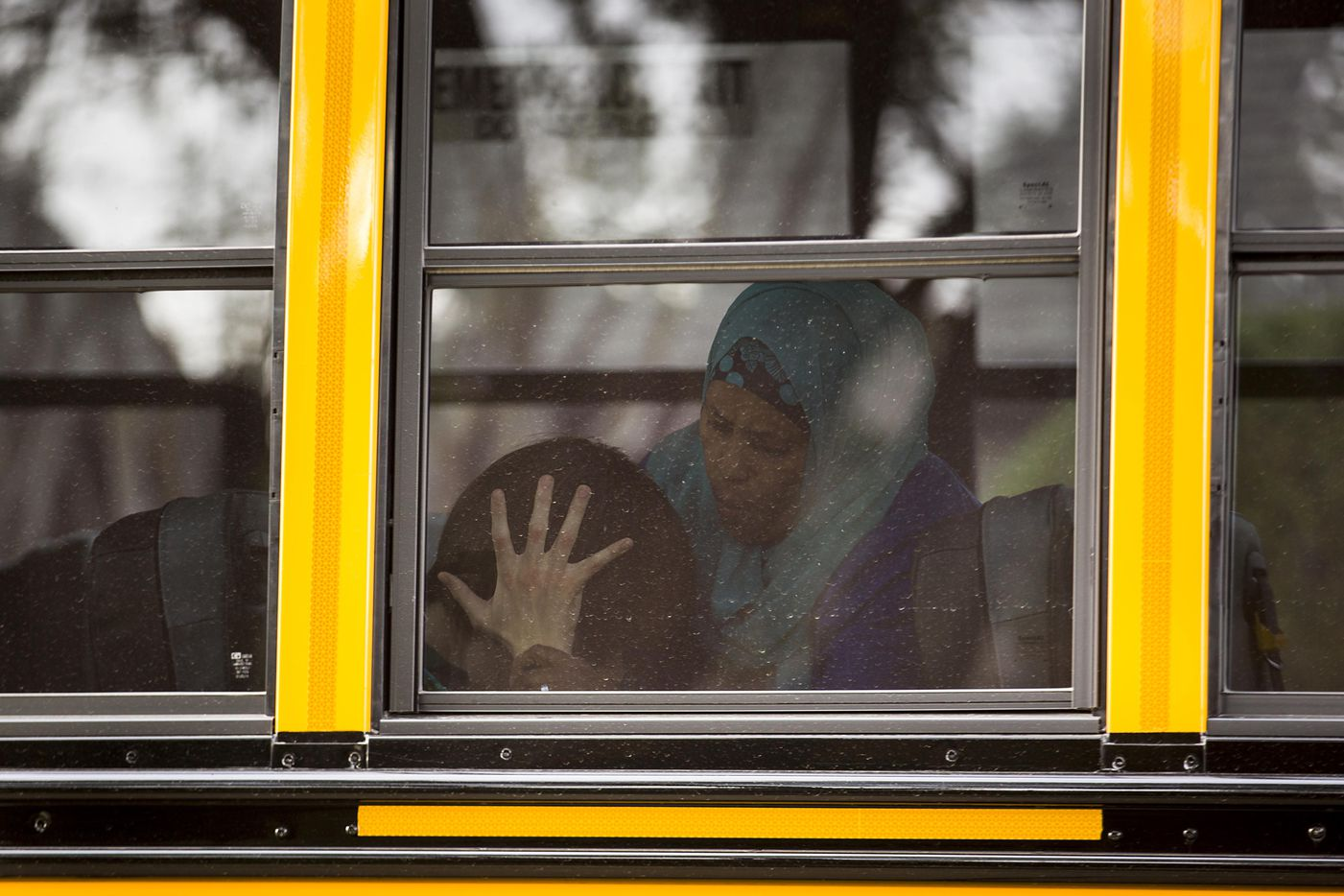 Kara Zartler covers her ears with her hands as the school bus pulls up in front of her family's home on Thursday, March 9, 2017, in Richardson. The 17-year old has severe autism and cerebral palsy. (Smiley N. Pool/The Dallas Morning News)