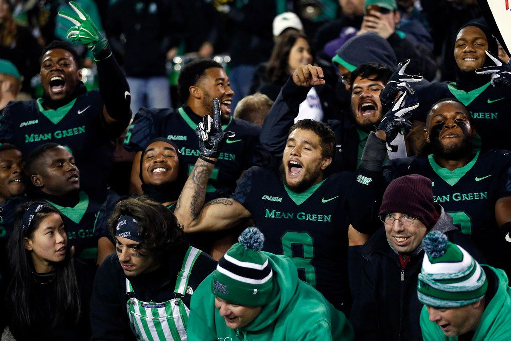 North Texas Mean Green football players celebrate their win in the student section of Apogee Stadium in Denton, Texas, Thursday, November 15, 2018. North Texas won, 41-38 over Florida Atlantic. (Tom Fox/The Dallas Morning News)