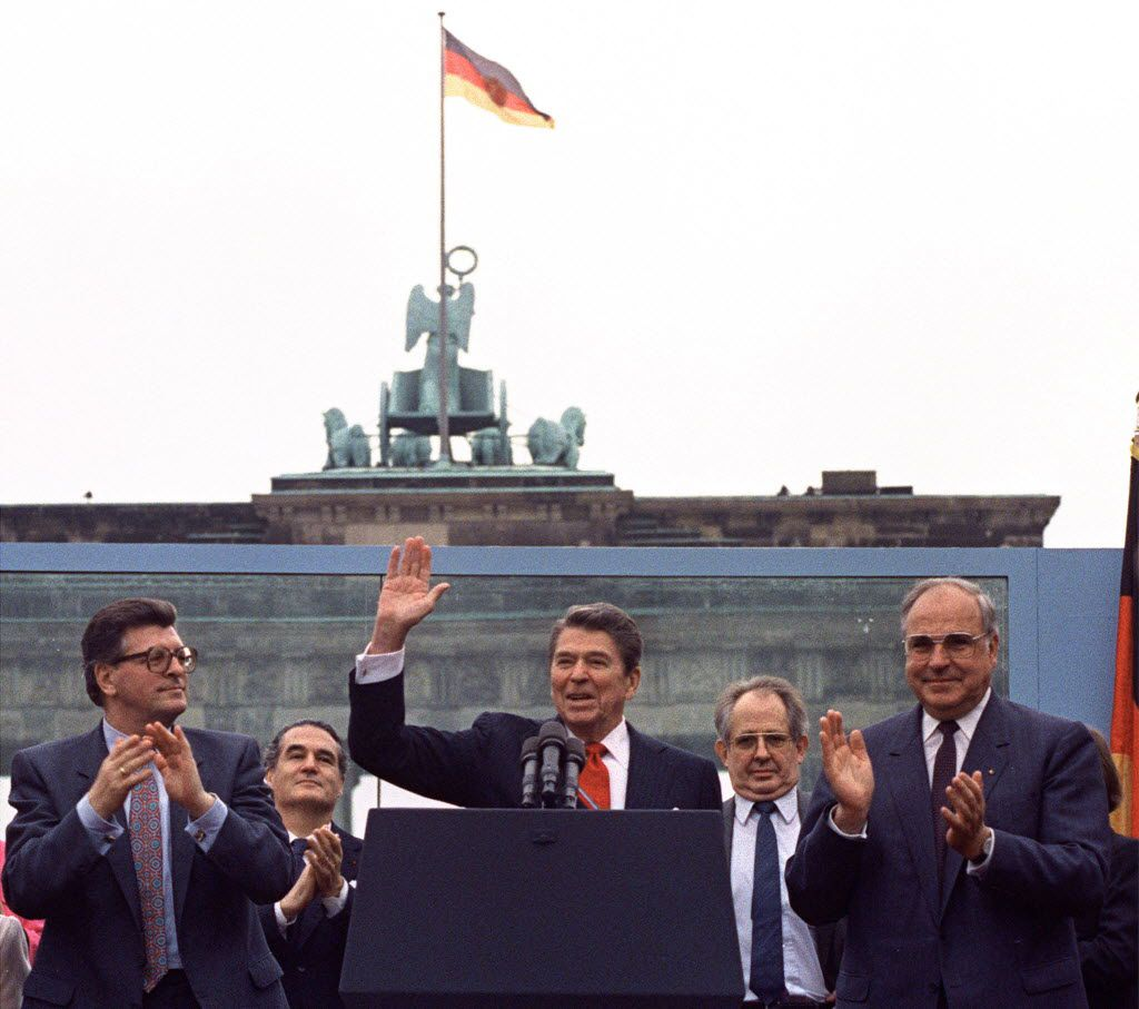 President Ronald Reagan acknowledged applause after speaking to an audience in front of the Brandenburg Gate in Berlin on June 12, 1987. Beside Reagan are the president of the German Parliament, Philipp Jenninger (left), and Germany's chancellor, Helmut Kohl (right). The 40th U.S. president served from 1981 to 1989.