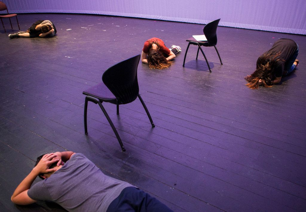 Cast members lay on the floor while practicing the opening scene of Shots Fired.