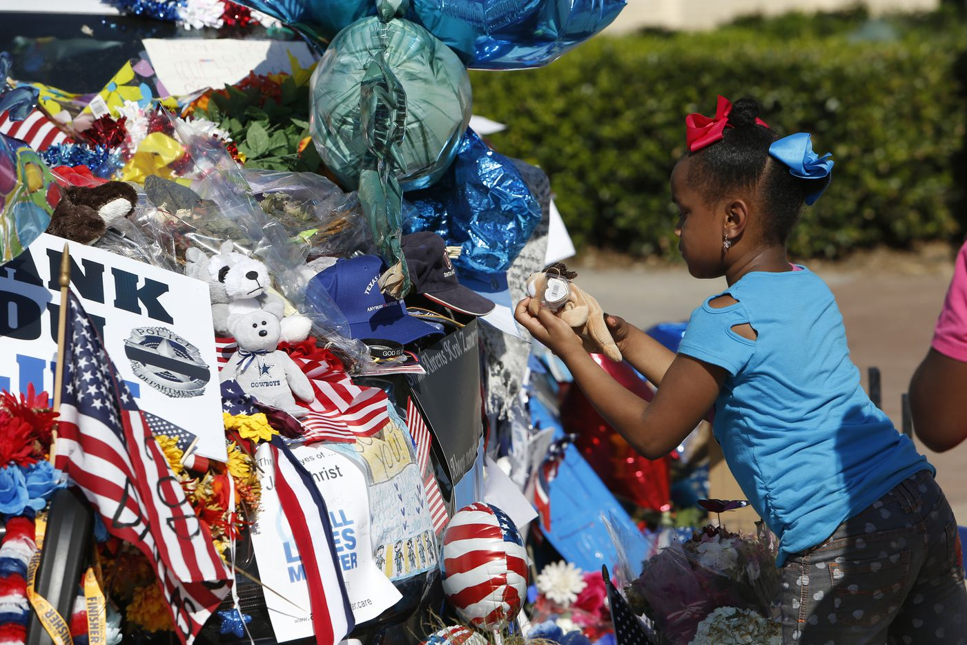 Willow Cook, 6, whose aunt is a jailer, takes a stuffed animal out to look at it before placing it back before before librarians from the Dallas Public Library collect items left at the Dallas Police Department memorial so that they may be archived and preserved, at  Jack Evans Police Headquarters in Dallas, TX July 19, 2016.