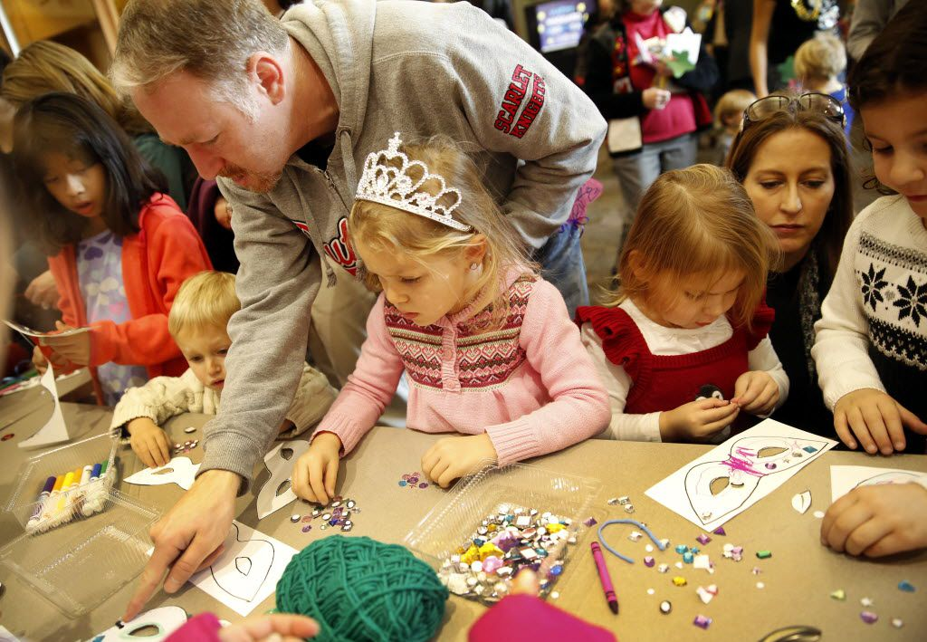Families make paper masks during the Noon Year's Eve Party for youngsters at the Haggard Library in Plano.