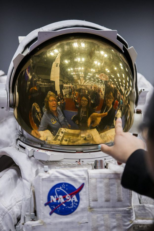 Yalu Ye of San Francisco points to the helmet of of a NASA space suit on display at the trade show at the Austin Convention Center during the 2015 SXSW interactive and film festival.
