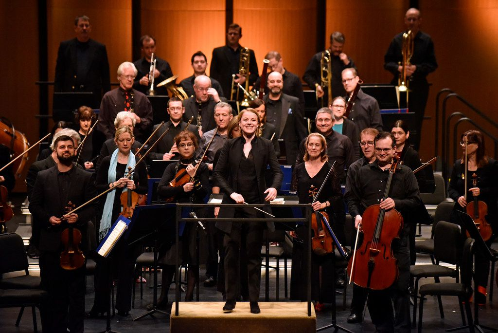Conductor Ruth Reinhardt, center, is introduced with the Dallas Symphony Orchestra before leading Rossini's Barber of Seville Overture in a ReMix concert Friday evening, March 2, 2018 at Moody Performance Hall in Dallas.