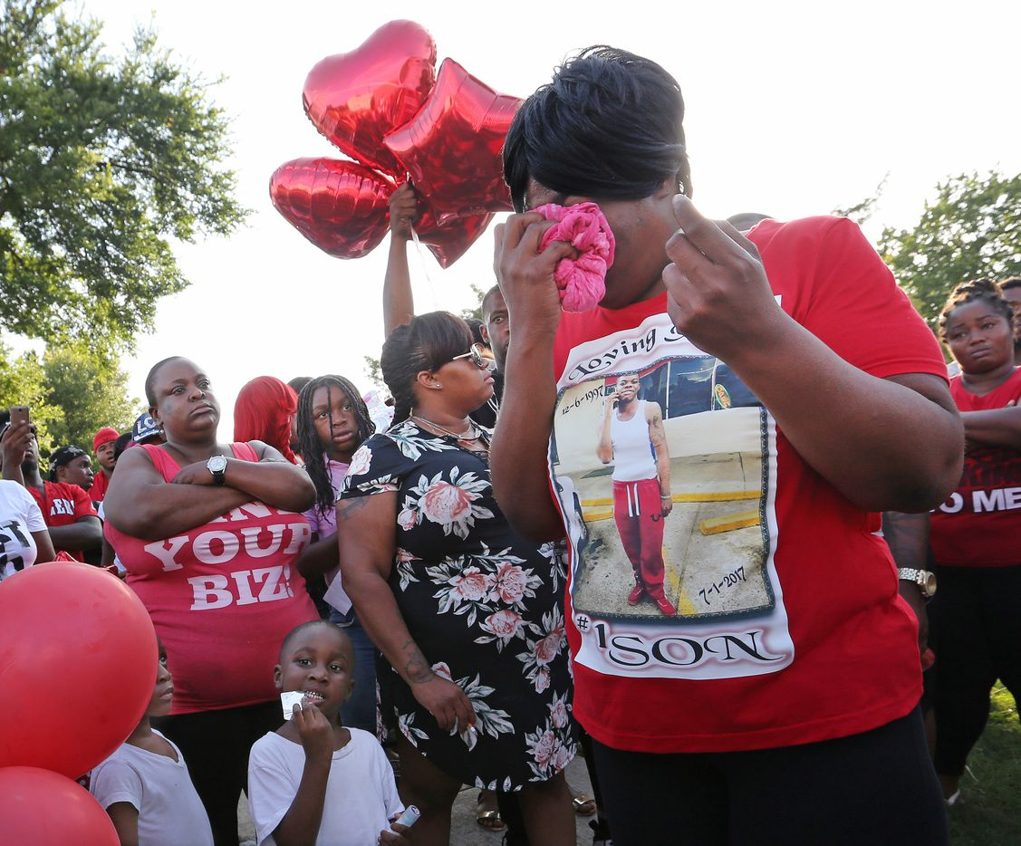 Mike Titus' mother, Angel Titus, wipes away tears and sweat as she talks with a crowd of friends, family and concerned neighbors at a vigil for her son in Cummings Park.