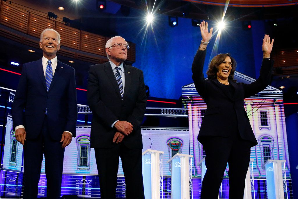 From left: Democratic presidential candidates Joe Biden, Sen. Bernie Sanders, I-Vt., and Sen. Kamala Harris, D-Calif., stand on stage for a photo op before the start of the the Democratic primary debate hosted by NBC News at the Adrienne Arsht Center for the Performing Arts on June 27, 2019, in Miami.