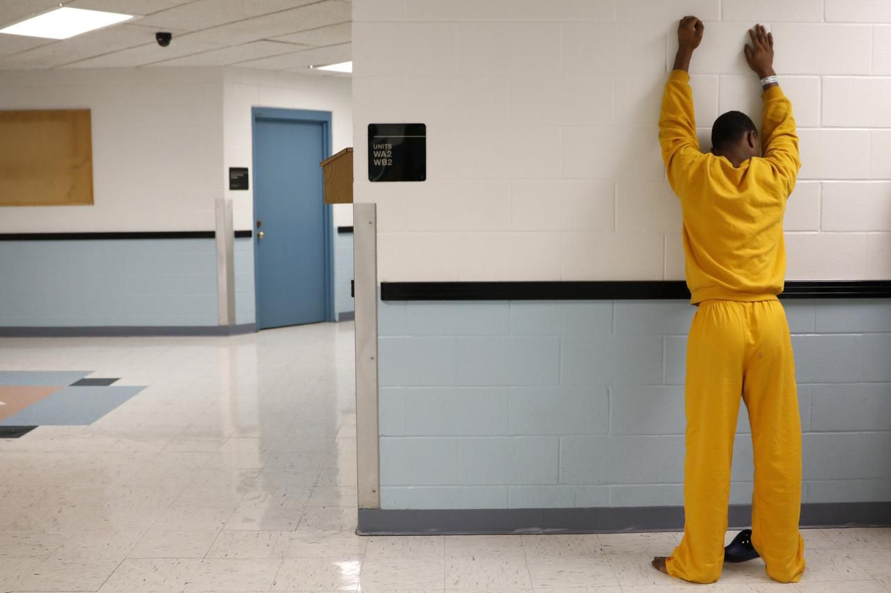 A juvenile inmate places his hands against the wall for a routine search following breakfast at the Henry Wade Juvenile Justice Center in Dallas on Feb. 18, 2015.