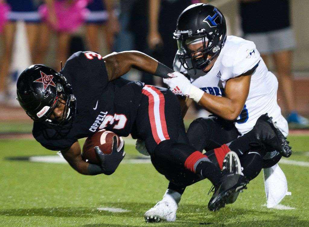 Coppell rebound Cam Williams (3) is brought down by Hebron defensive back Vinson Miller (13) during the first half of a high school football game on Friday, Oct. 4, 2019, in Coppell, Texas. (Smiley N. Pool/The Dallas Morning News)