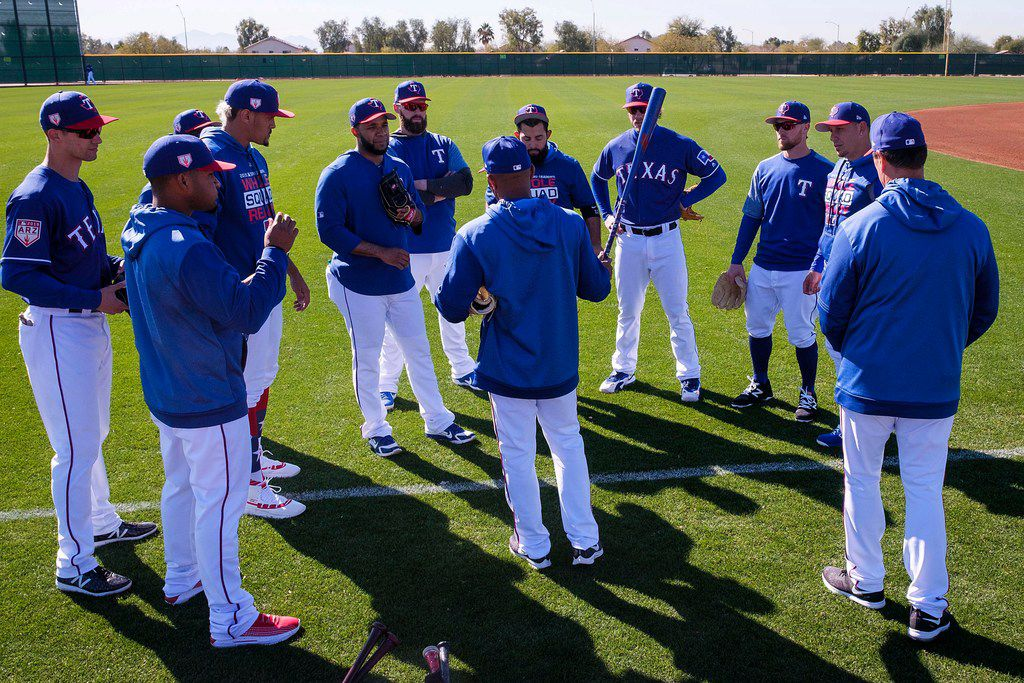Texas Rangers position players huddle around third base coach Tony Beasley before beginning a defensive drill during a spring training workout at the team's training facility on Wednesday, Feb. 20, 2019, in Surprise, Ariz.. (Smiley N. Pool/The Dallas Morning News)