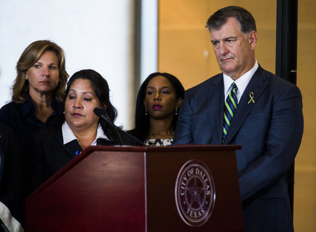 Dallas Mayor Mike Rawlings (right) listens to Texas Governor Greg Abbott (not pictured) speak during a press conference on Friday, July 8, 2017 at Dallas City Hall in downtown Dallas, Texas. (Ashley Landis/The Dallas Morning News)