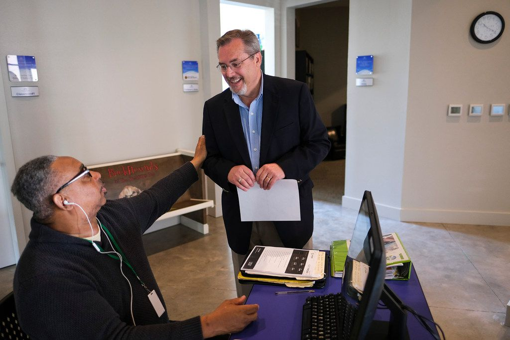 Samaritan Inn CEO Rick Crocker (standing) talks with client Edward Thornton Jr. as he works at a computer at the nonprofit's new homeless center on Friday.