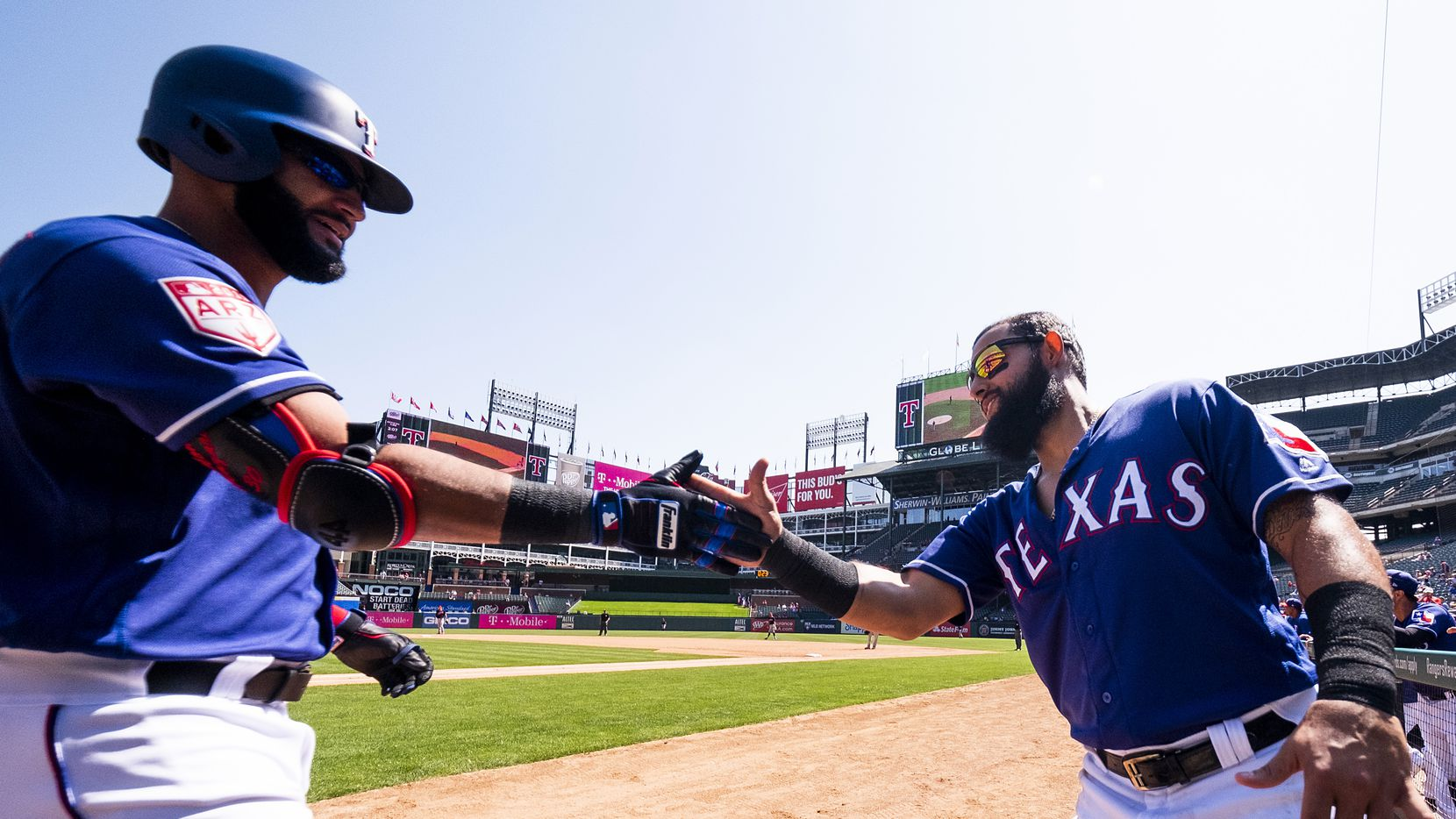 Texas Rangers outfielder Nomar Mazara (left) celebrates with second baseman Rougned Odor after hitting a three-run home run during the third inning of a spring training baseball game against the Cleveland Indians at Globe Life Park on Tuesday, March 26, 2019, in Arlington.