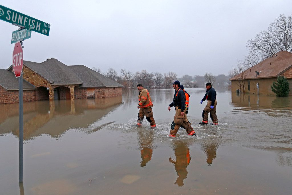 Rockwall firefighters walk in the flooded water on Lakeside Drive while searching the area in Rockwall, Texas, Thursday, Feb. 22, 2018.
