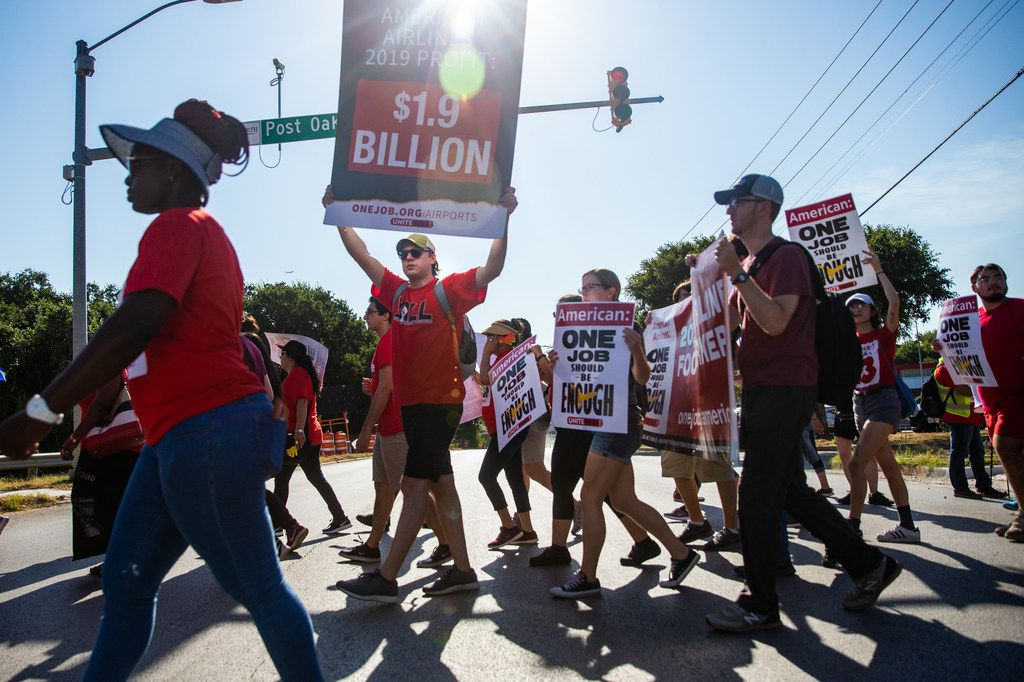 Jason Lopez (center) and other protesters march to the new corporate headquarters for American Airlines in Fort Worth to protest employee wages and benefits at LSG Sky Chefs.