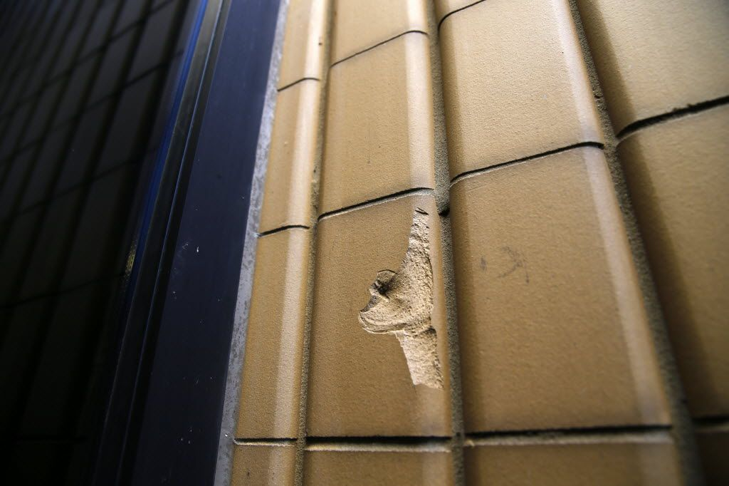 A bullet hole is seen in the brick facade outside the Elm St. entrance of El Centro College in downtown Dallas, July 19, 2016.  The gunman made his entrance through this door after killing 4 police officers on the street. (Tom Fox/The Dallas Morning News)