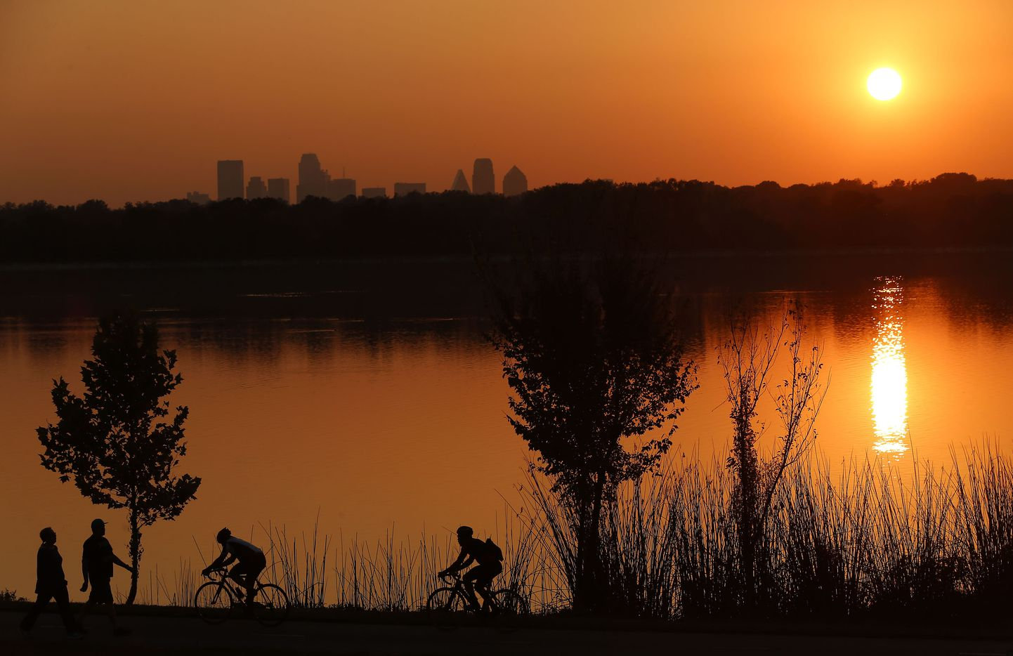 People and cyclists on the path at White Rock Lake as the sun sets Nov. 3, 2017. The photo was shot from the garden near the Test Pavilion at Dallas Arboretum. The downtown Dallas skyline can be seen in the distance.