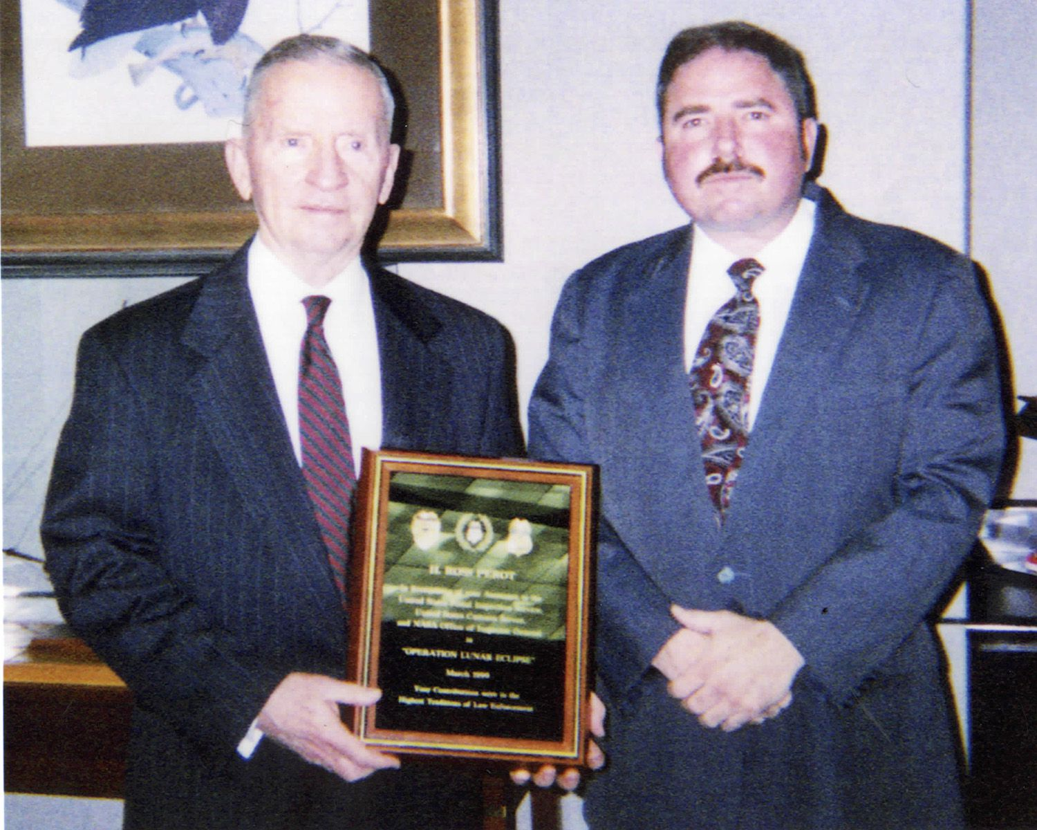 Ross Perot (left) is presented with a plaque by special agent Joseph Gutheinz (right) honoring him for his contribution to Operation Lunar Eclipse.