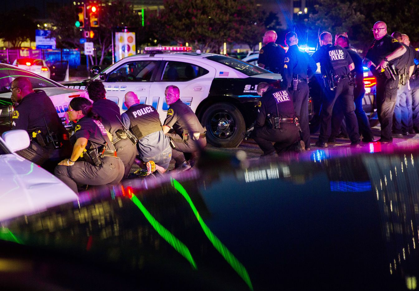 At 9:07 p.m., Dallas officers took cover behind police vehicles at the intersection of South Lamar and Jackson streets as the attack continued.