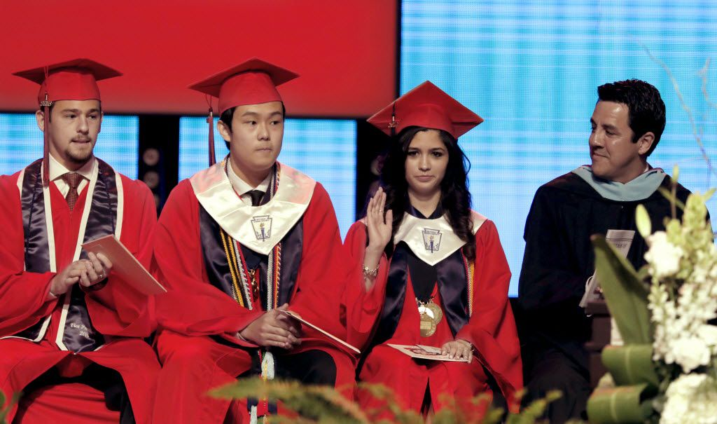 Prior to delivering her speech, Valedictorian Larissa Yanin Martinez waves to the crowd as she is introduced on stage during the McKinney Boyd High School Commencement ceremony at Prestonwood Baptist Church on Friday, June 3, 2016, in Plano, Texas. With her are (from left) Baron Phillips, Senior Class student council Vice President; Salutatorian Anthony Zhang Liu; and Cruz Saenz, Associate Principal of the school.