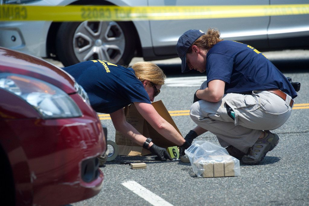FBI Evidence Response Team members mark evidence at the scene of a multiple shooting in Alexandria, Va., Wednesday, June 14, 2017, involving House Majority Whip Steve Scalise of La., and others during a congressional baseball practice. (AP Photo/Cliff Owen)