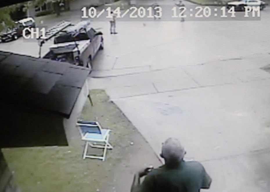Dallas Police Department officers (obscured, behind date/time stamp at top) walk up to Bobby Bennett (top center, by front of truck) in a chair in a cul-de-sac in Rylie.