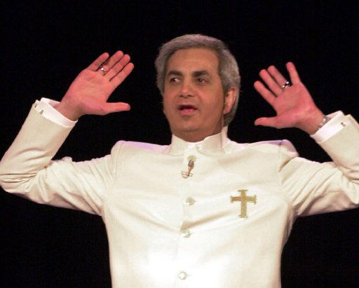 Televangelist Benny Hinn raises his hands in prayer during a service at the Blaisdell Concert Hall in Honolulu in 2002. (Ronen Zilberman/The Associated Press)
