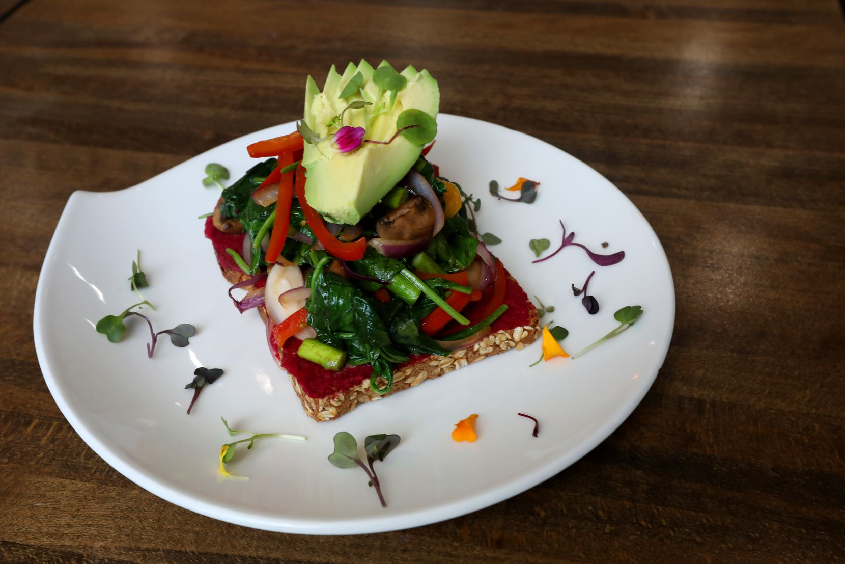 The veggie toast at Nest Cafe includes avocado, pan-seared mushrooms, spinach, asparagus, tomato and beet hummus.