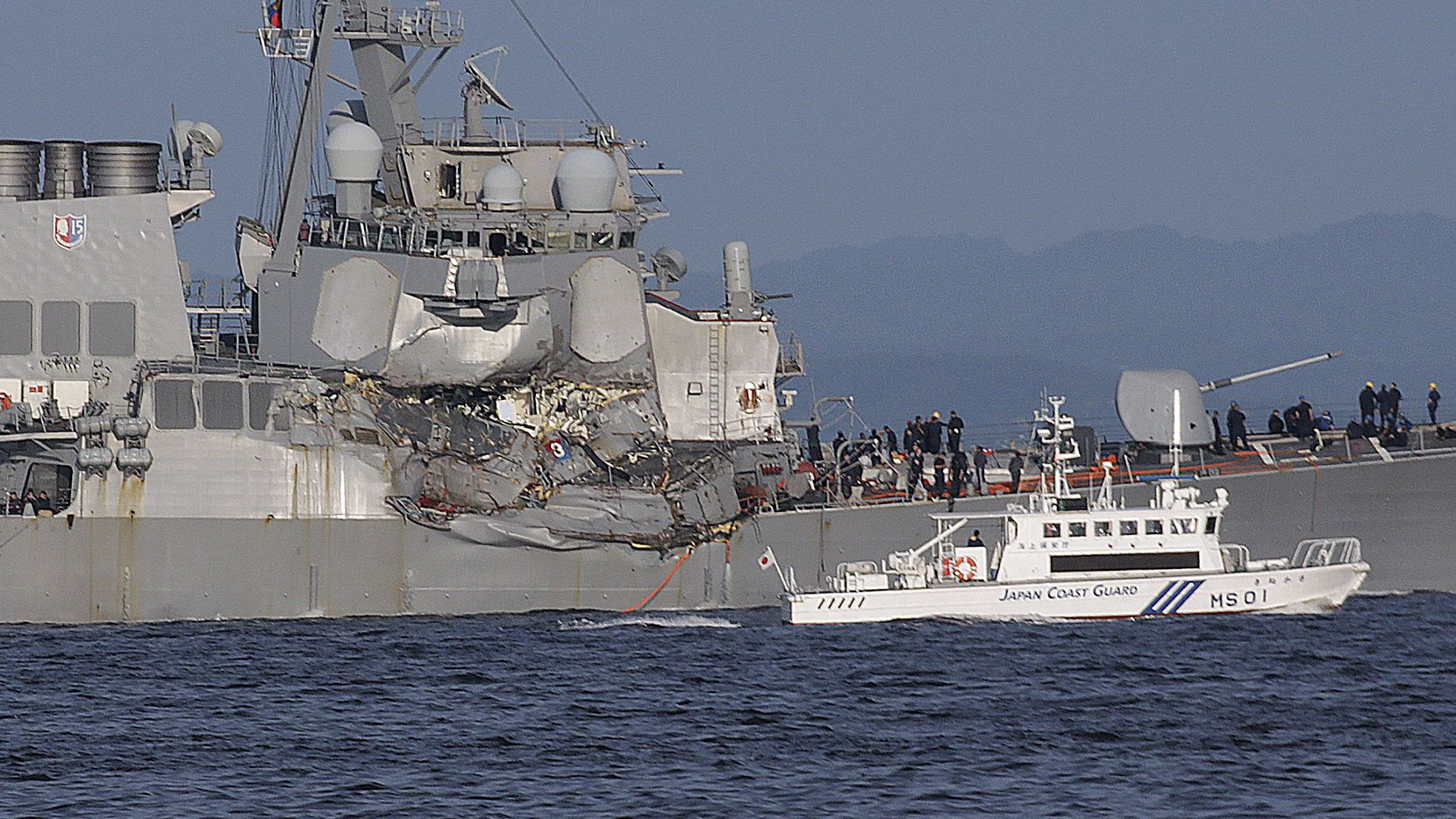 In this Saturday, June 17, 2017, file photo, a Japan Coast Guard ship, foreground, navigates the damaged USS Fitzgerald near the U.S. Naval base in Yokosuka, southwest of Tokyo, after the U.S. destroyer collided with the Philippine-registered container ship ACX Crystal in the waters off the Izu Peninsula. The USS Fitzgerald was back at its home port in Japan after colliding before dawn Saturday with a container ship four times its size, while the coast guard and Japanese and U.S. military searched for seven sailors missing after the crash. (AP Photo/Eugene Hoshiko, File)