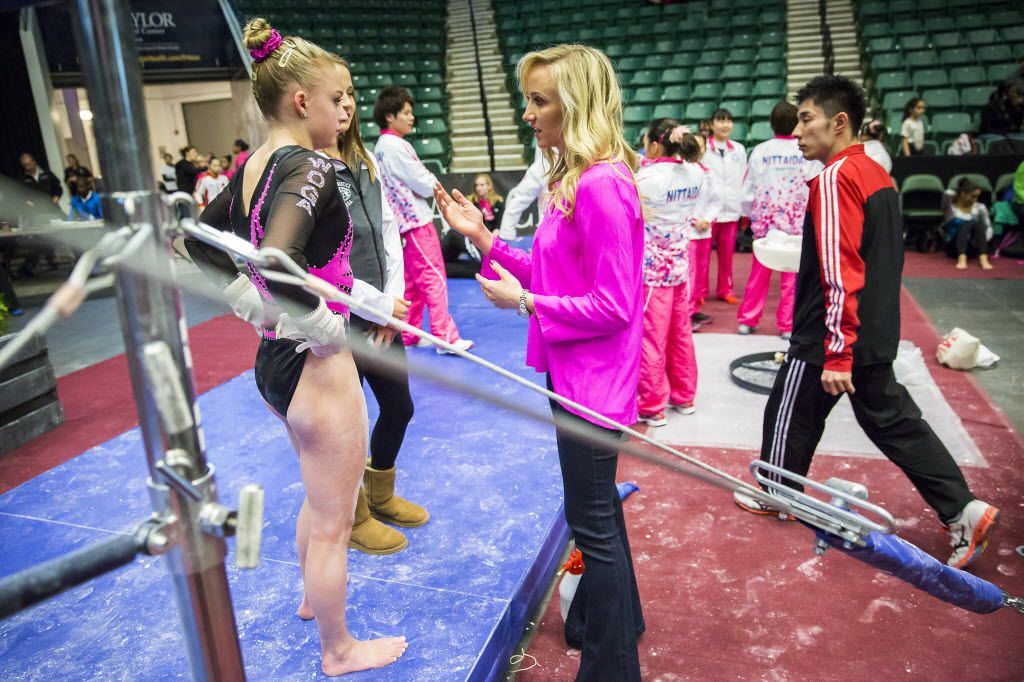Nastia Liukin, center, talks with gymnast Alyssa Baumann, left, before Baumann competes during the  WOGA Classic at the Dr. Pepper Arena on Saturday, Feb. 14, 2015, in Frisco.