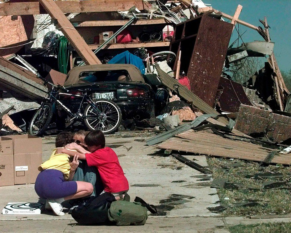 In this March 29, 2000 file photo, Tracy-Lynn Clough-Rian, center, gets a hug from her neighbors Theresa Smith and Preston Smith, 9, in front of Tracy-Lynn's tornado-destroyed home in Arlington, Texas.