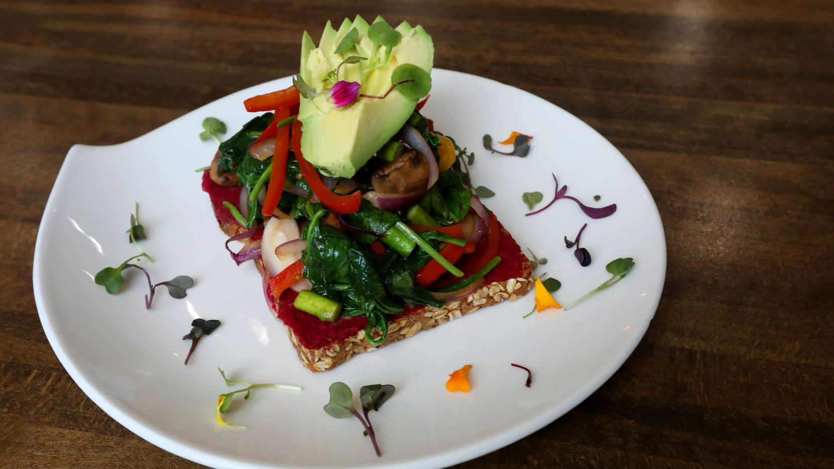 Veggie Toast, with avocado, pan seared mushroom, spinach, asparagus, tomato and beet hummus on multigrain bread at The Nest Cafe in Frisco, Texas, Thursday, Oct. 17, 2019. (Anja Schlein/Special Contributor)