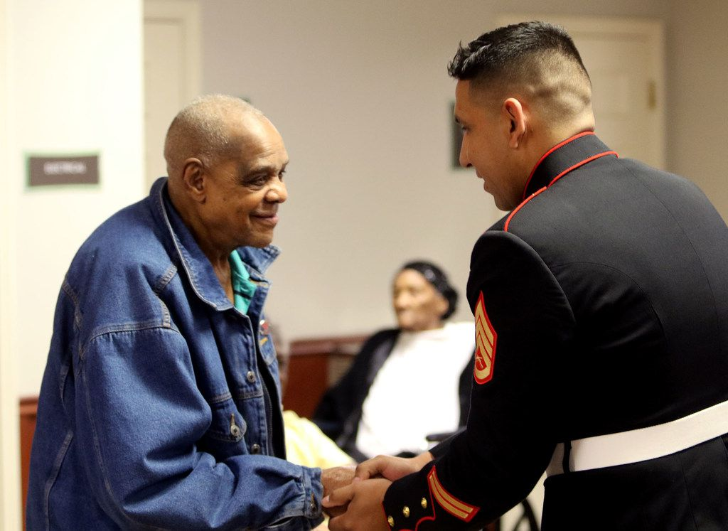 Sam Johnson, a U.S. Army veteran who fought in World War II, shakes Marine Corps Staff Sgt. Eder Orozco's hand after receiving a pin and certificate at the Lennwood Nursing & Rehab Veterans Day pinning ceremony.