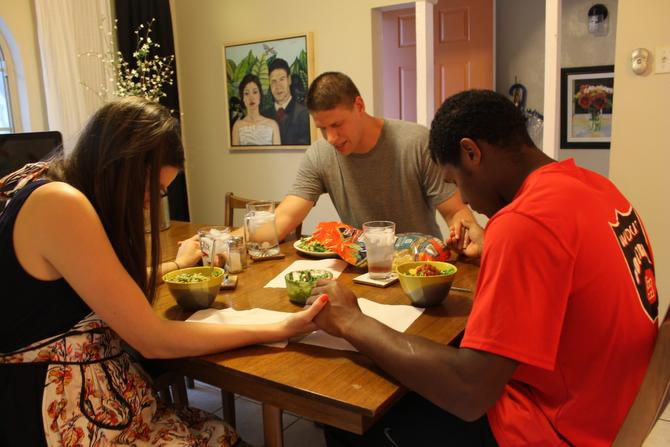 Garza (middle) says a blessing before dinner with his wife, Sara, and Lake Highlands High School sophomore LaQuantis Davis at the Garzas' home in Lake Highlands. Garza founded the Forerunner Mentoring Program, a nonprofit that focuses on providing young boys with absent fathers with a positive male role model through mentoring relationships. Davis is mentored by Garza.
