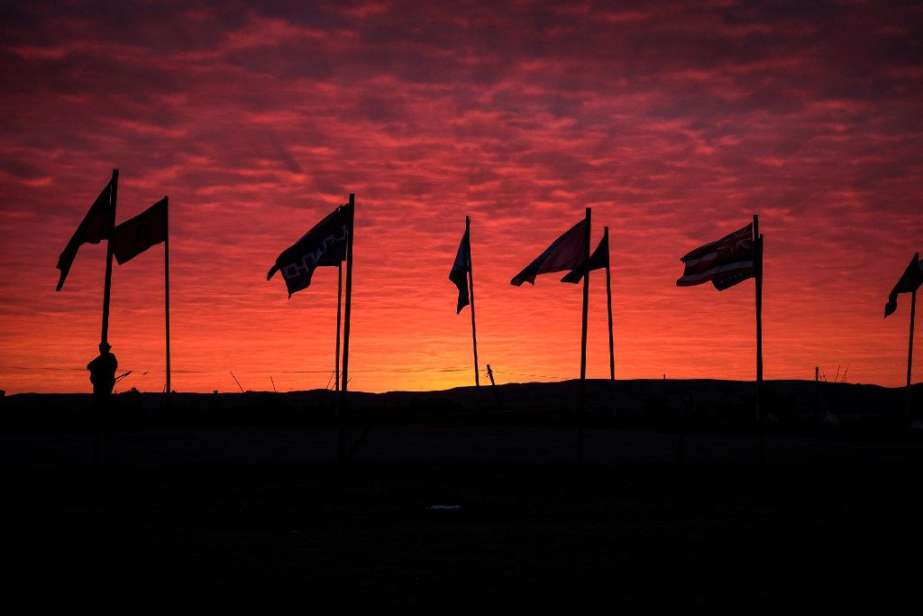 Morning sunrise at the entrance to the Standing Rock camp is lined with dozens of flags from Native American and Indigenous communities around the world  in Cannonball, North Dakota on Wednesday, Sep 14th, 2016. Standing Rock has seen hundreds of whole families and activists visit, eager to take part in the historic gathering. Construction has been halted after the Obama administration decision to suspend construction on a controversial oil pipeline in North Dakota.  (Jeenah Moon/Special Contributor)