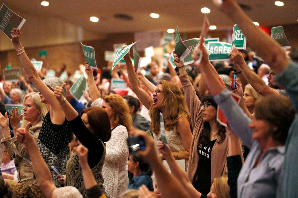 """People show their """"agree,"""" signs during a town hall meeting with Rep. Pete Sessions, R-Dallas in the auditorium of Richardson High School in Richardson on Saturday, March 18, 2017. (Vernon Bryant/The Dallas Morning News)"""