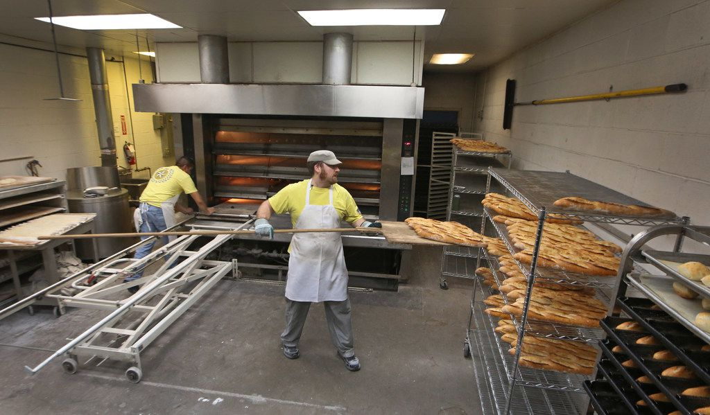 Fidel Morales Cisneros (left) and Jonathan Brown make long, narrow loaves of French bread known as baguettes at Empire Baking Company.