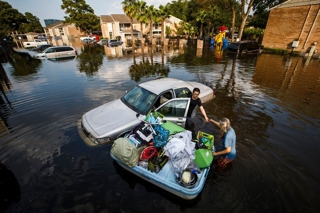 After loading a paddle boat with belongings from his apartment, Jeff Liu is helped by his mother Rhoda as he retrieves items from his car at his west Houston apartment, still inundated with flood waters from Hurricane Harvey, on Saturday, Sept. 2, 2017, in Houston.