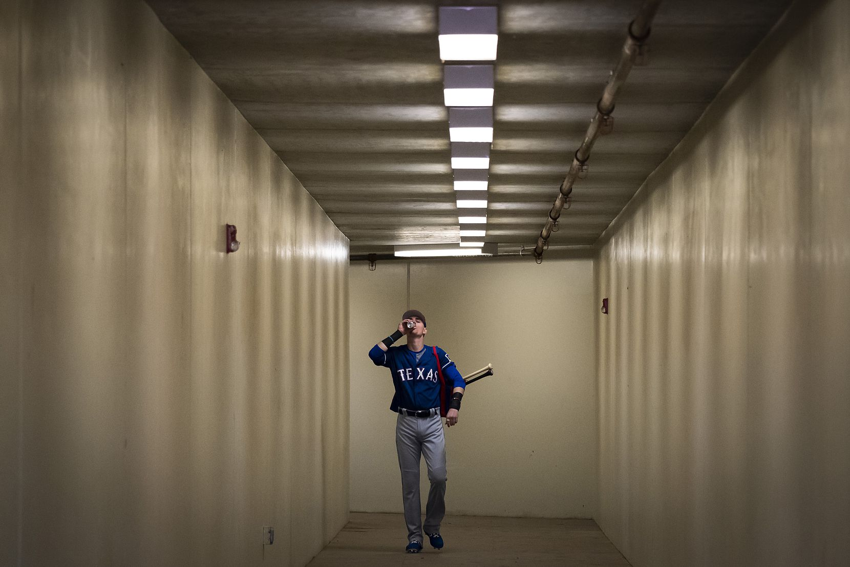 Texas Rangers outfielder Carlos Tocci downs an energy drink as he walks from the clubhouse to the stadium for the team's first spring training game against the Kansas City Royals on Feb. 23 at Surprise Stadium in Surprise, Ariz.