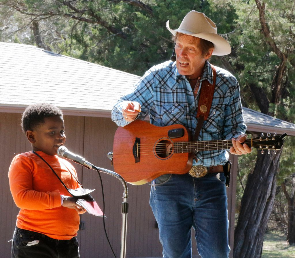 """Samuel Bedford takes the stage to help out """"Cowboy Bob"""" Ackerman  during Cowboy Camp in Cedar Hill. About 70 kids from DISD took part in team building, story time and singing."""
