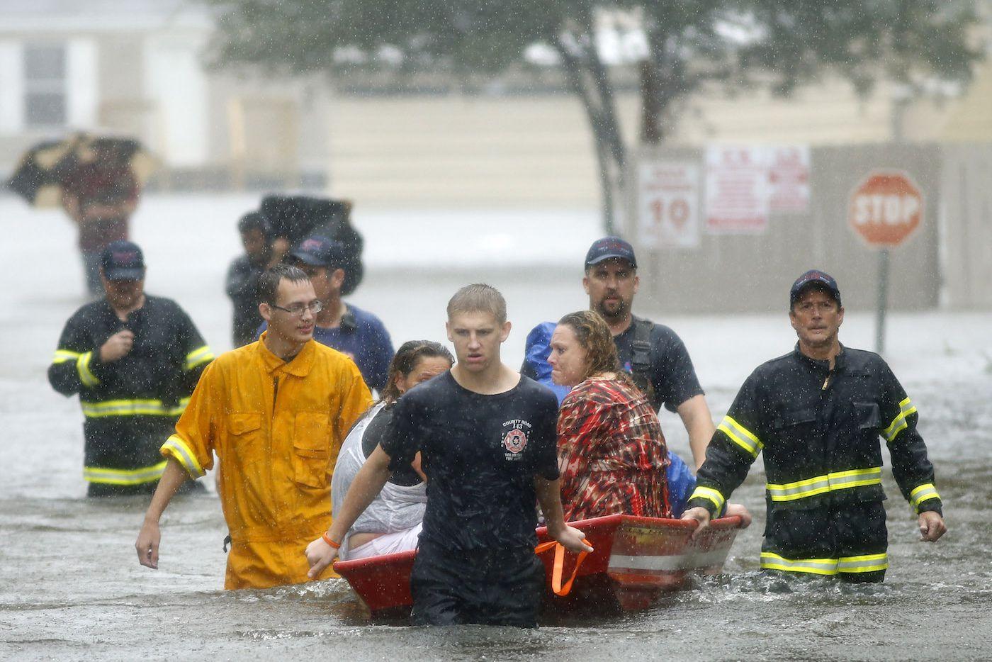 Voluntarios del Departamento de Bomberos y Rescate County Road 143 ayudan a rescatar a personas atrapadas por las inundaciones en Pearland, Texas. TOM FOX/ DMN.