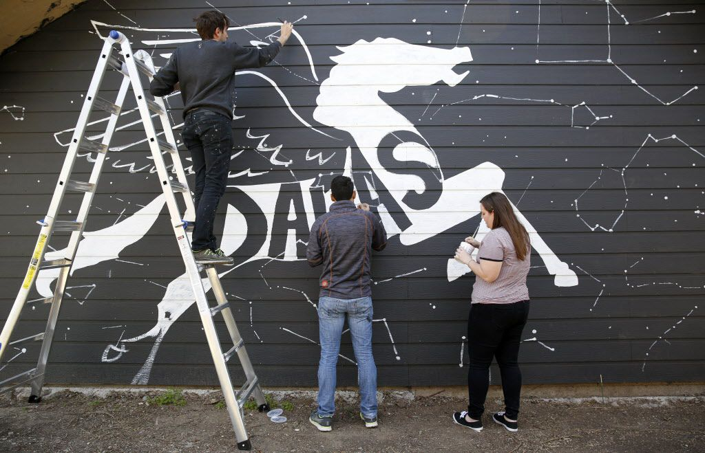 Will Heron, also known as Wheron, (far left) works on his mural Dallaxy, with help from Jorge Alcala and Sarah Duke at The Platform.