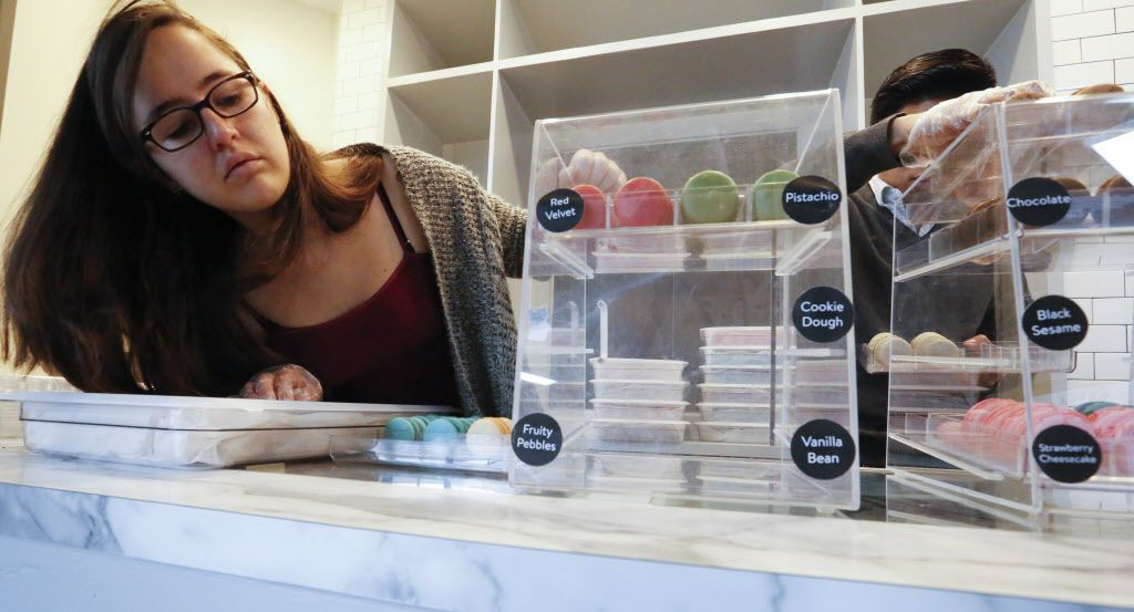 Maria Moreno, left, and Jonathan King place macarons on the counter at Chelles Macarons at The Market's soft opening at the Dallas Farmers Market Friday December 11, 2015.  (Ron Baselice/The Dallas Morning News)   [ This is located in the building formerly called Shed 2 at the Dallas Farmers Market ]