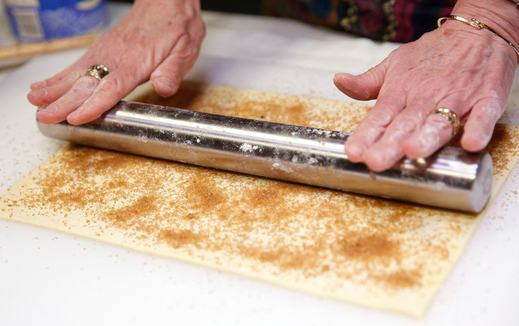 After getting brown sugar sprinkled onto puff pastry, use a roller to press in the sugar to the dough in order to make palmiers.