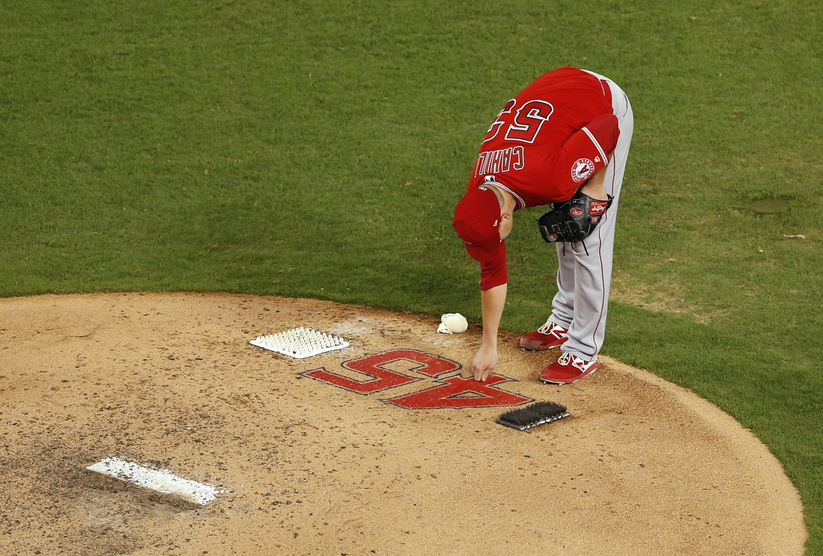 Los Angeles Angels pitcher Trevor Cahill (53) touches the number of Los Angeles Angels Tyler Skaggs (45) at the mound before pitching against the Texas Rangers during the fifth inning of play at Globe Life Park in Arlington on July 2, 2019. Los Angeles Angels Tyler Skaggs was found dead in his Southlake hotel room on July 1 before the scheduled game against the Rangers.