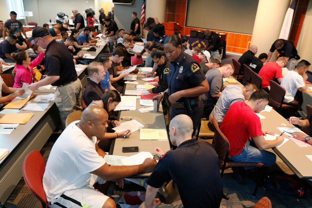 Dallas police detective David Marchioni, right foreground, helps Antwain Robinson from Arkansas with his paperwork at the Jack Evans Police Headquarters in Dallas on Thursday, Sept. 7. About 80 candidates are applying to be Dallas police officers.