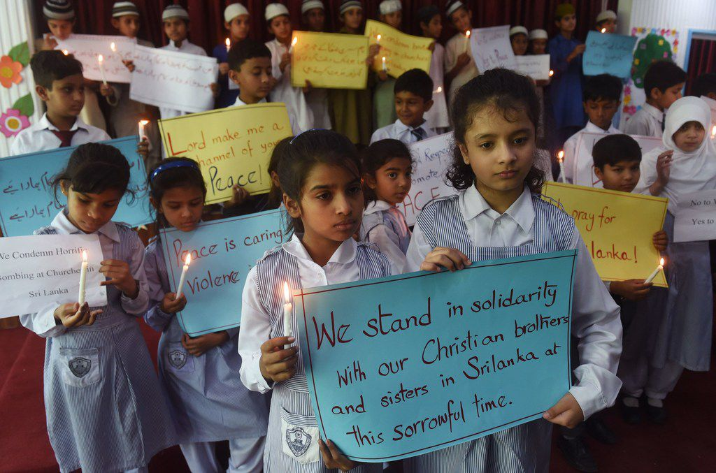Pakistani Christian and Muslim students carry placards and candles as they pay tribute to the Sri Lankan blasts victims, at St. Marys High School in Lahore on April 23, 2019. - Sri Lanka began a day of national mourning on April 23 with three minutes of silence to honor more than 300 people killed in suicide bomb blasts that have been blamed on a local Islamist group.
