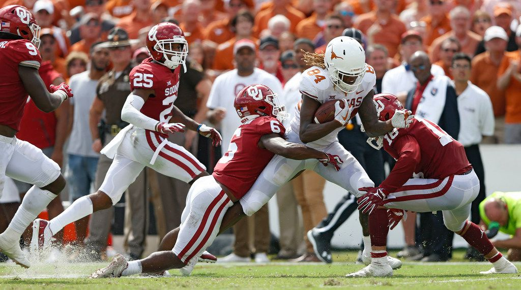 Texas Longhorns wide receiver Lil'Jordan Humphrey (84) is tackled by Oklahoma Sooners cornerback Tre Brown (6) and Oklahoma Sooners linebacker Curtis Bolton (18) during the second half of play at the Cotton Bowl in Dallas on Saturday, October 6, 2018. Texas Longhorns defeated Oklahoma Sooners 48-45. (Vernon Bryant/The Dallas Morning News)