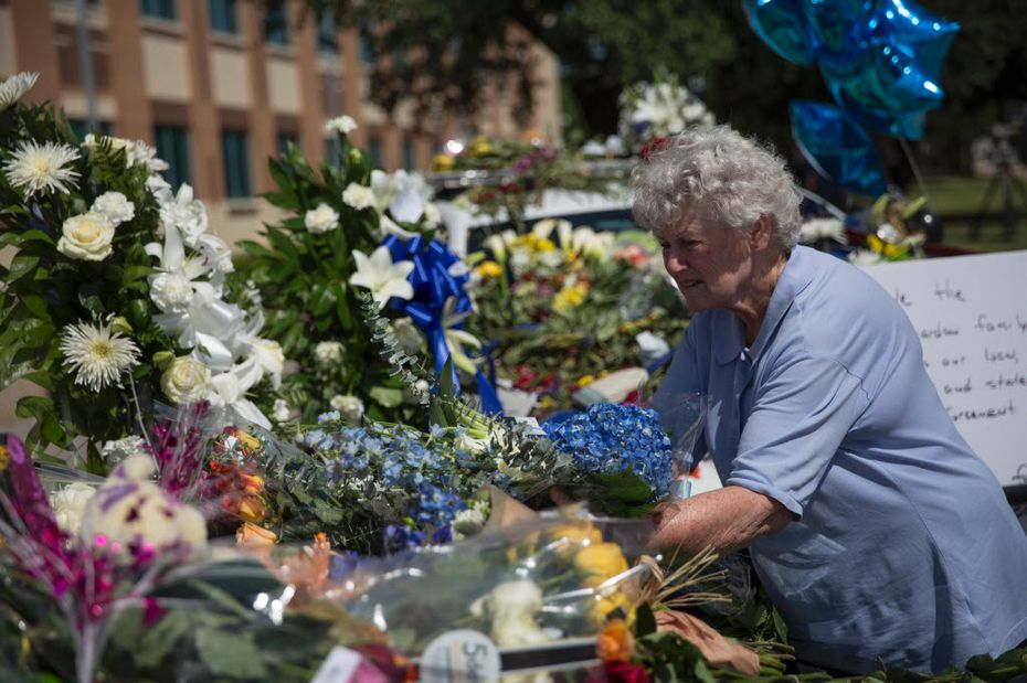 A woman places flowers at a memorial outside the Dallas police headquarters.