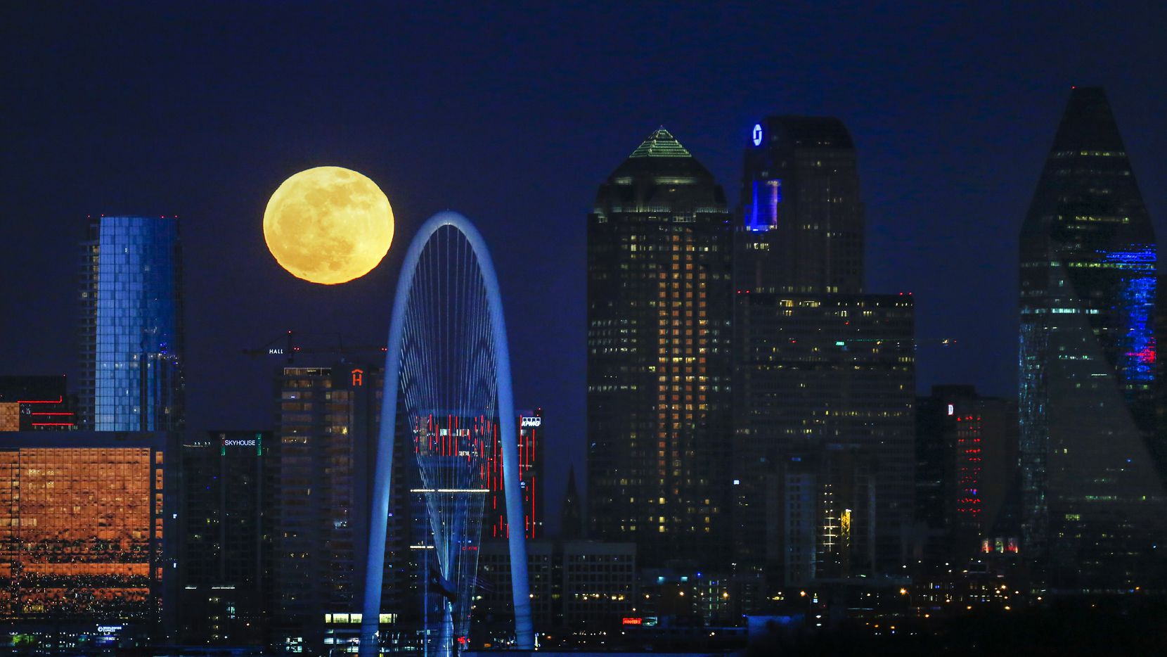 The full moon rises over the Dallas skyline in December 2018.