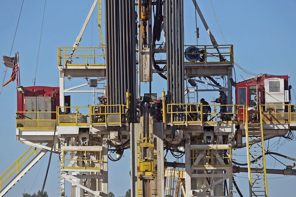 File photo of of workers standing on the platform of a fracking rig in the Permian Basin oil field in Midland.